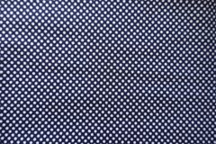 Symmetric dots pattern on blue fabric. Symmetric geometric dots pattern on blue fabric royalty free stock photography