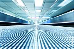 Symmetric moving blue escalator inside contemporary airport Royalty Free Stock Photo