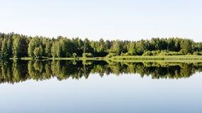 Symmetric reflections on calm lake Stock Photography