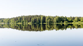 Symmetric reflections on calm lake Royalty Free Stock Images