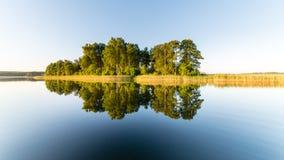 Symmetric reflections on calm lake Stock Photos