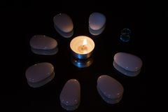 Symmetric stones flower by candlelight. In the dark Royalty Free Stock Photography