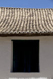 Symmetrical composition with wall, window and roof. PORTO SEGURO, BA, BRAZIL - MARCH 13, 2016 - Wall and roof of tiles of the the historic city of Porto Seguro Royalty Free Stock Image