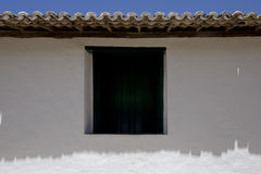Symmetrical composition with wall, window and roof. PORTO SEGURO, BA, BRAZIL - MARCH 13, 2016 - Wall and roof of tiles of the the historic city of Porto Seguro Royalty Free Stock Photos