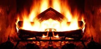 Symmetrical Fireplace. Closeup of roaring log fire in fireplace Stock Photo