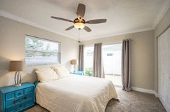 Symmetrical Master. Elegant bed in master suite featuring two turquoise side tables with canvas lamps. Warm beige carpeting and access to the outside patio royalty free stock photo