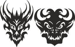 Symmetrical monster head tattoos. Set of aggressive symmetrical tribal monster head tattoo sketches Royalty Free Stock Photos