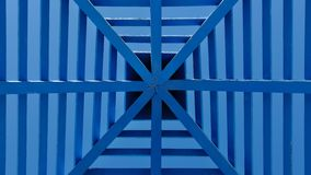 Symmetrical pattern obtained from a blue patio wooden cover or a pergola with a roof against clear blue sky royalty free stock images