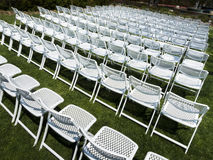 Symmetrical Pattern Of White Folding Chairs At Outdoor Garden Event. These white folding chairs at an outdoor garden event make a great background pattern Royalty Free Stock Images