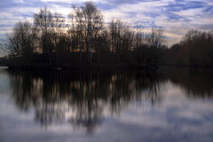 Symmetrical reflections landscape. Reflections of an island and sky in the water Royalty Free Stock Photos