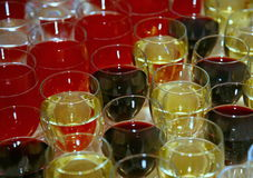 symmetrical rows of cocktail glasses filled with different colored drinks on the bar. Royalty Free Stock Photo