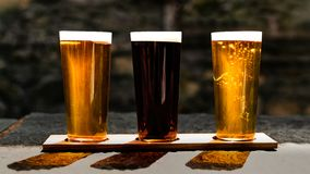 Three Beers in the Sun. A symmetrical shot of three different beers, two golden, one ruby, lined up outside in the sun stock images