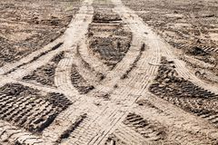 Symmetrical traces of car tires on dirty field Royalty Free Stock Photography