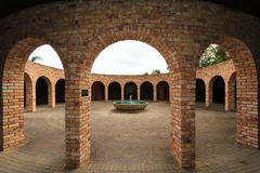 Symmetrical View of Circular Courtyard, Looking Through Brick Arches. A Mediterranean / Middle Eastern inspired brick courtyard with a fountain in the middle stock images