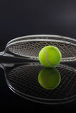 Symmetrical view of tennis racket on ball with reflection Stock Photo