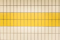 Yellow and white tiles in a subway station in Düsseldorf, Germany. Symmetrical Yellow and white tiles in a subway station in Düsseldorf, Germany stock image