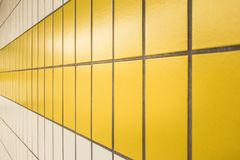 Yellow and white tiles in a subway station in Düsseldorf, Germany. Symmetrical Yellow and white tiles in a subway station in Düsseldorf, Germany royalty free stock photography