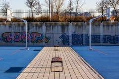 Symmetrie auf einem blauen Basketball plaground mit Bänke lizenzfreies stockbild