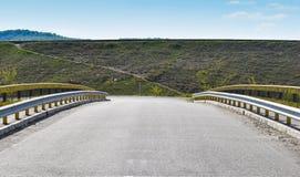 Symmetrisch beeld langs de lege brug op de asfaltweg stock fotografie