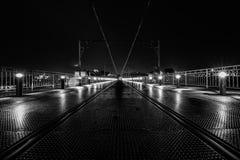 Symmetrische tramsporen op Dom Luis I Brug bij nacht op de achtergrond, Porto, Portugal Zwart-wit beeld stock foto