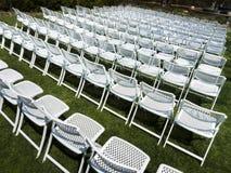 Symmetrisk modell av vita hopfällbara stolar på den utomhus- trädgårds- händelsen Royaltyfria Bilder