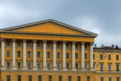 Symmetry in architecture. View from the water to a beautiful yellow building with columns on the embankment of St. Petersburg, Russia, symmetry, architecture Royalty Free Stock Photography