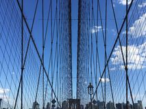 The symmetry of the Brooklyn bridge. Cable-stayed and buildings with blue sky, New York Stock Photo