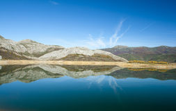 Symmetry reflected in water. Riaño dam, Spain Royalty Free Stock Photo