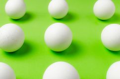 Symmetry of white eggs on bright light green background. Abstraction Stock Photo