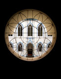 Symmetry window and building. A study of symmetry seen from a circular window with radially symmetrical pattern on the window frame.  View from window is of a Royalty Free Stock Photo