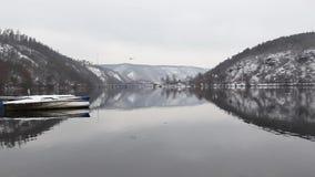 Symmetry winter landscape and yellow train. Single track railway bridge over the Vltava river, Czech Republic . Winter landscape stock video footage