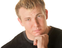 Sympathetic Blond Man. Concerned blond muscular man over white background and hand on chin stock photography
