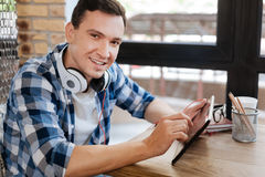 Sympathetic cheerful guy playing with his gadget Stock Images