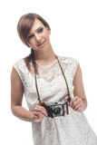 Sympathetic female photographer. With a gentle smile on her face standing looking off frame while holding her camera in her hands, isolated on white Royalty Free Stock Image
