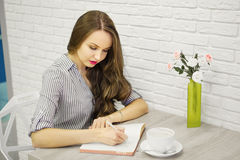 Sympathetic girl holding pen and writting in sketch-book. Sympathetic girl holding elegant pen and writing in sketchbook. Empty cup on saucer and vase with Royalty Free Stock Image