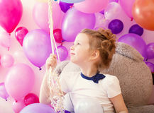 Sympathetic little girl holding bunch of balloons Royalty Free Stock Photography