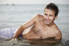 Sympathetic smile of man. Young man posing on Italian bech in water and relaxing in summer sun stock photos