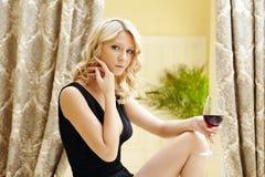 Sympathischer blonder trinkender Wein im Restaurant Stockfotografie