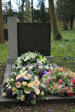 Sympathy flowers on a grave. Multicolored sympathy flowers on an old grave Royalty Free Stock Image