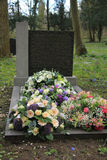 Sympathy flowers on a grave. Multicolored sympathy flowers on an old grave Royalty Free Stock Images