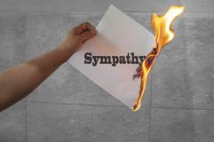Sympathy word text on fire with burning paper. In hand stock photography