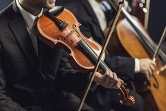 Symphonic string orchestra performing on stage. Professional symphonic string orchestra performing on stage and playing a classical music concert, violinist in royalty free stock image