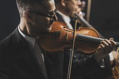 Symphonic string orchestra performing on stage. Professional symphonic string orchestra performing on stage and playing a classical music concert, violinist in stock photography