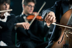Symphony orchestra: cello player close-up. Symphony orchestra performing with cello player hand close-up Stock Image