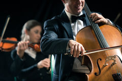 Symphony orchestra performance: celloist close-up. Cello professional player with symphony orchestra performing in concert on background Stock Photography