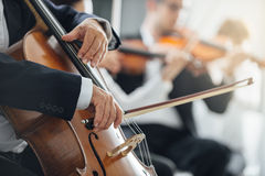 Symphony orchestra performance, string section. String section of classical music symphony orchestra performing, cellist playing on foreground, hands close up Royalty Free Stock Images