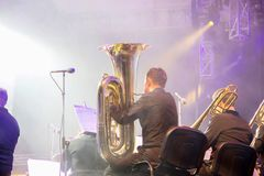 Symphony orchestra on the stage, orchestral brass section, behind the scenes shoot.Tubaist in black shirt blow in big brass tube stock image