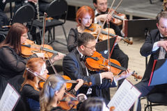 Symphony orchestra on stage. Violin group plays Royalty Free Stock Images