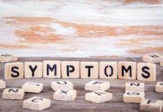 Symptomen van houten brieven op houten achtergrond stock foto's