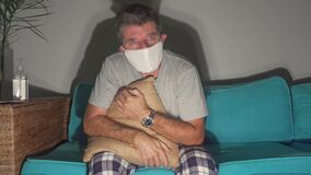 Symptoms of covid-19 virus infection - scared and worried man in mask feeling sick at home couch coughing and suffering chest pain